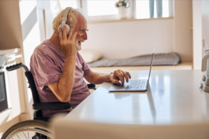 Elder wheelchair user with headphones and a computer